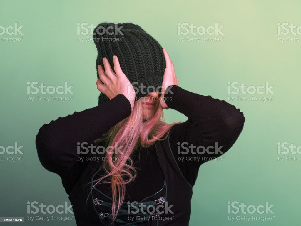 A young apathetic woman covered her face with a knitted hat stock photo