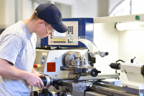 young apprentice in vocational training working on a turning machine in the industry young apprentice in vocational training working on a turning machine in the industry machinery stock pictures, royalty-free photos & images