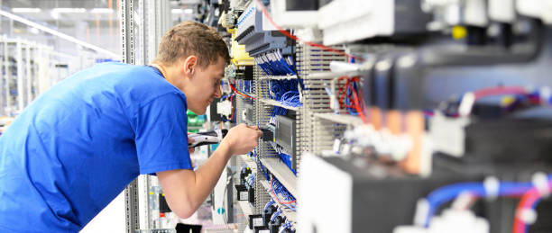young apprentice worker in an industrial company assembling electronic components in the mechanical engineering of a modern factory stock photo