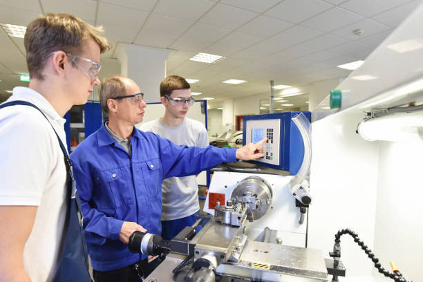 young apprentices in technical vocational training are taught by older trainers on a cnc lathes machine - vocational training stock photos and pictures