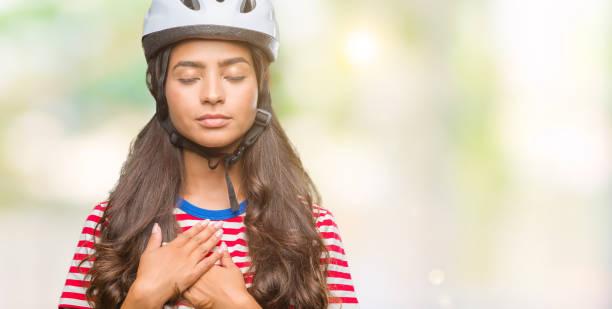junge arabische radfahrer frau tragen schutzhelm über isolierte hintergrund lächelnd mit die hände auf die brust mit geschlossenen augen und dankbar geste auf gesicht. gesundheitskonzept. - die wahrheit tut weh stock-fotos und bilder