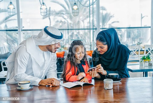 istock Young Arab family enjoying with smartphone at cafe 472869308