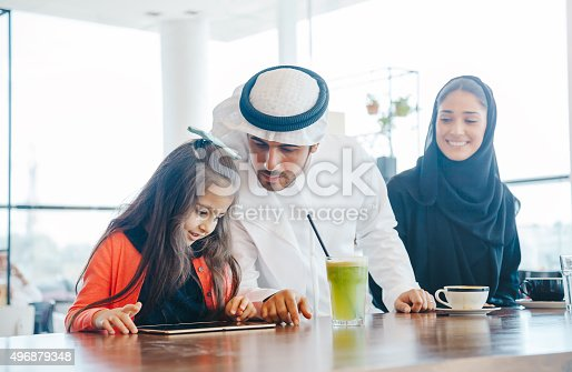 istock Young Arab family enjoying with tablet pc at cafe 496879348