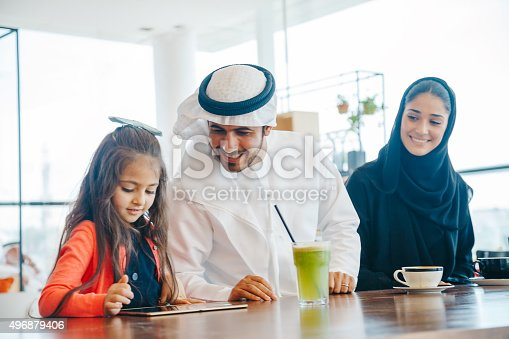 istock Young Arab family enjoying with tablet pc at cafe 496879406