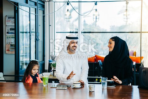 istock Young Arab family enjoying with tablet pc at cafe 496879984