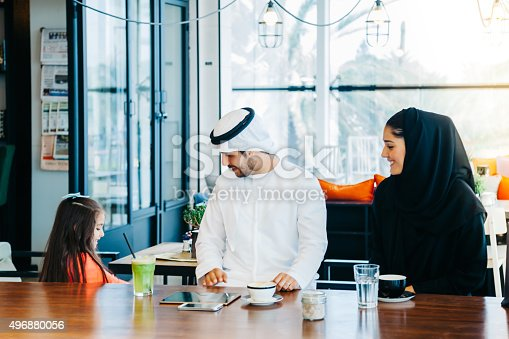 istock Young Arab family enjoying with tablet pc at cafe 496880056