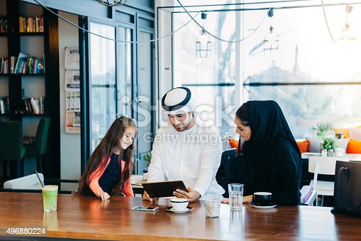 istock Young Arab family enjoying with tablet pc at cafe 496880224
