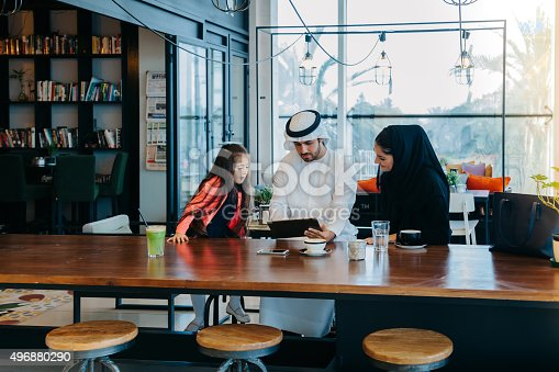 469930796 istock photo Young Arab family enjoying with tablet pc at cafe 496880290