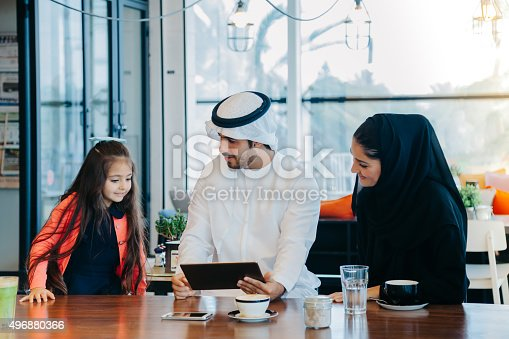 istock Young Arab family enjoying with tablet pc at cafe 496880366