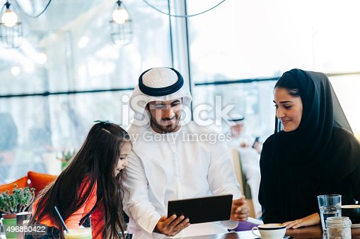 469930796 istock photo Young Arab family enjoying with tablet pc at cafe 496880422
