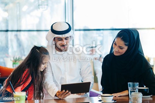 istock Young Arab family enjoying with tablet pc at cafe 496880474