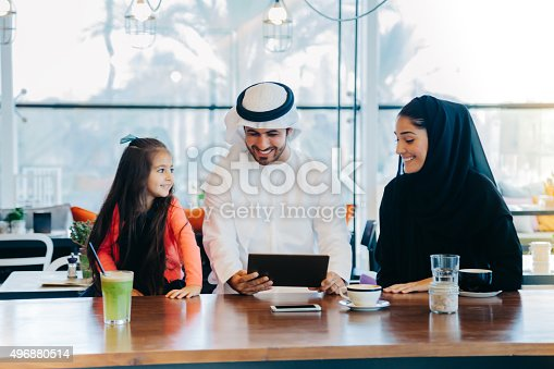 469930796 istock photo Young Arab family enjoying with tablet pc at cafe 496880514