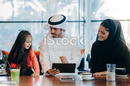 istock Young Arab family enjoying with tablet pc at cafe 496880568