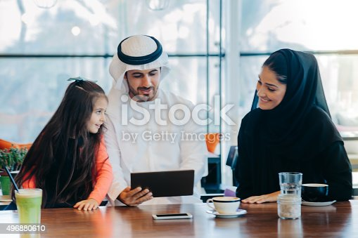 istock Young Arab family enjoying with tablet pc at cafe 496880610
