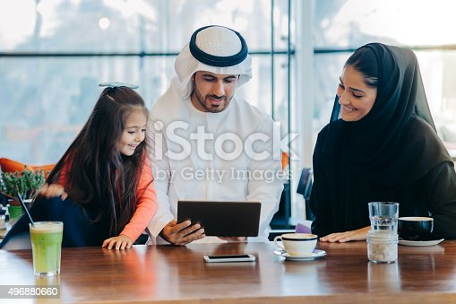 istock Young Arab family enjoying with tablet pc at cafe 496880660