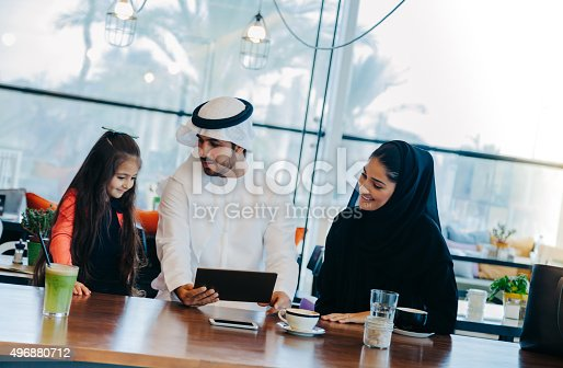 469930796 istock photo Young Arab family enjoying with tablet pc at cafe 496880712
