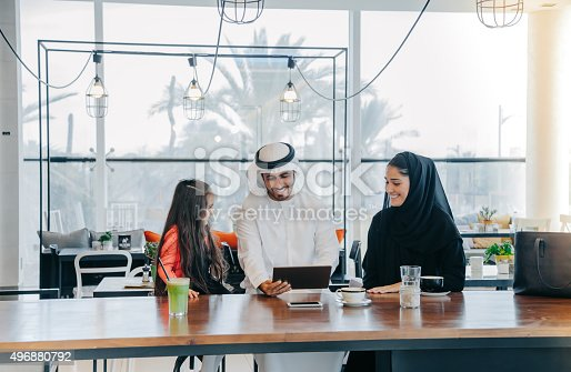 istock Young Arab family enjoying with tablet pc at cafe 496880792