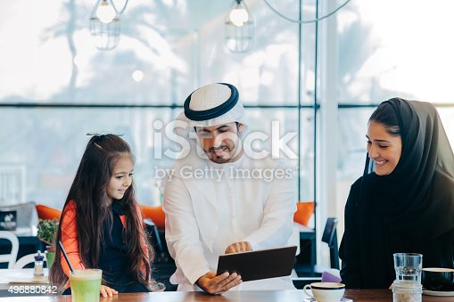istock Young Arab family enjoying with tablet pc at cafe 496880842