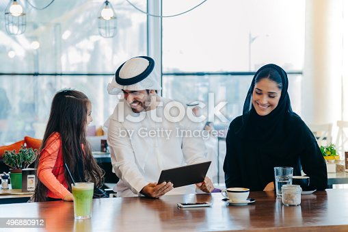 469930796 istock photo Young Arab family enjoying with tablet pc at cafe 496880912