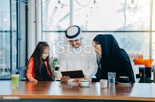 istock Young Arab family enjoying with tablet pc at cafe 496880964