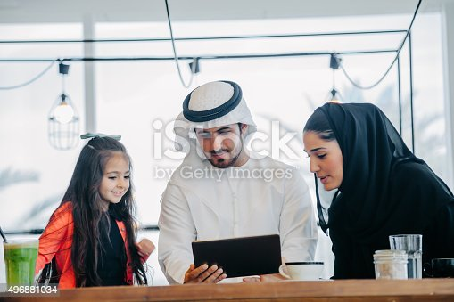 istock Young Arab family enjoying with tablet pc at cafe 496881034