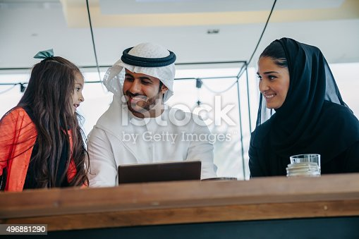 istock Young Arab family enjoying with tablet pc at cafe 496881290
