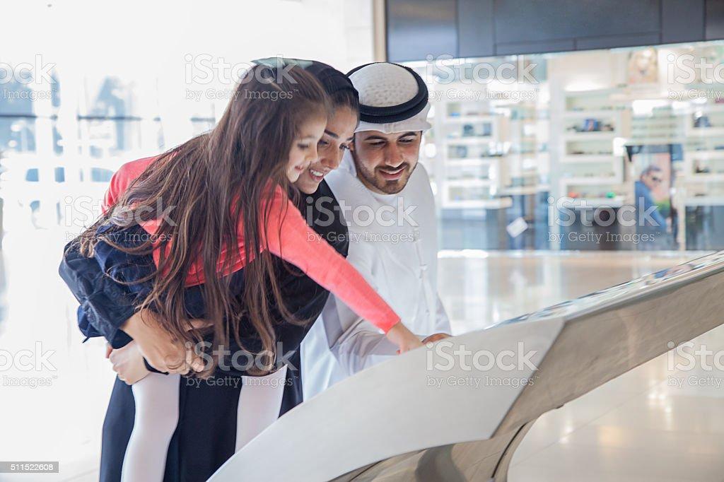 Young Arab family using information display at mall stock photo