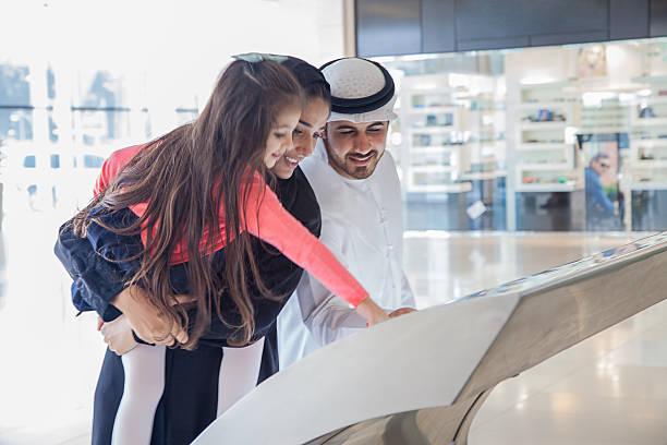 jovem família usando árabe informações ver a centro comercial - tv e familia e ecrã imagens e fotografias de stock