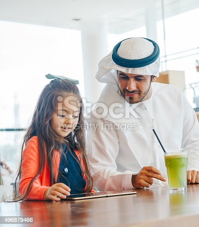 istock Young Arab father and daughter enjoying  tablet pc at cafe 496879466