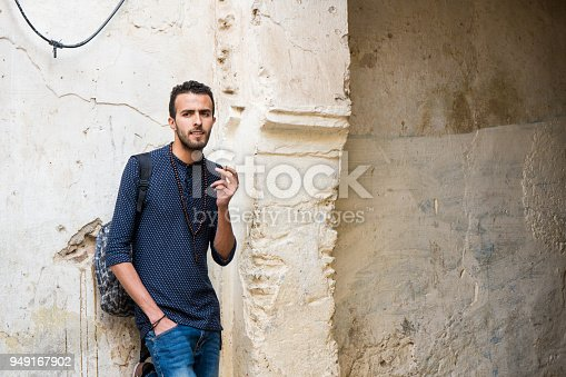 istock Young Arab man smoking a cigarette in casual clothing standing by the ruined wall 949167902