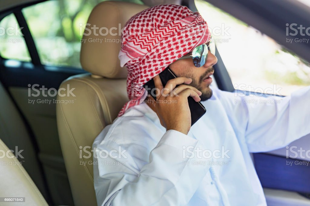 Young Arab using his mobile phone while driving stock photo