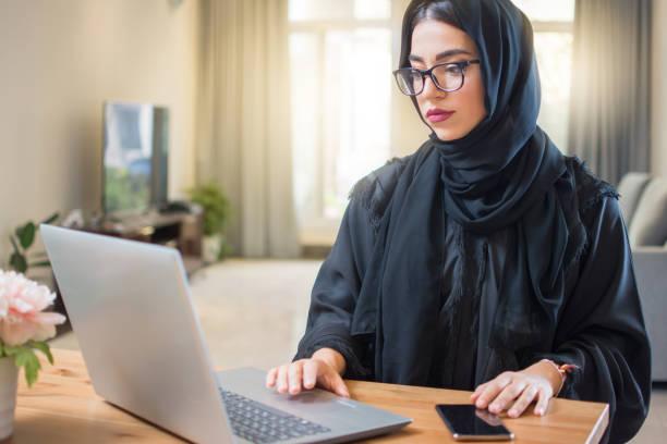 年輕的阿拉伯婦女戴頭巾在家裡的筆記本電腦工作。 - emirati woman 個照片及圖片檔