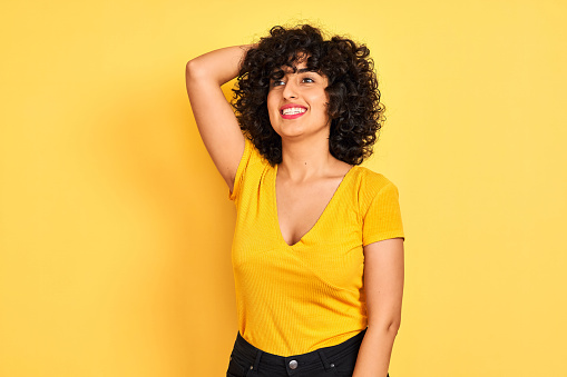 629077968 istock photo Young arab woman with curly hair wearing t-shirt standing over isolated yellow background smiling confident touching hair with hand up gesture, posing attractive and fashionable 1173825348