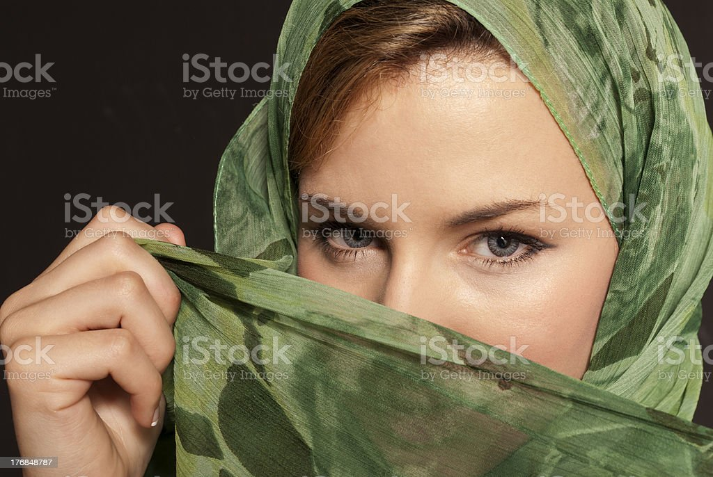 Young arab woman with veil showing her eyes on dark stock photo