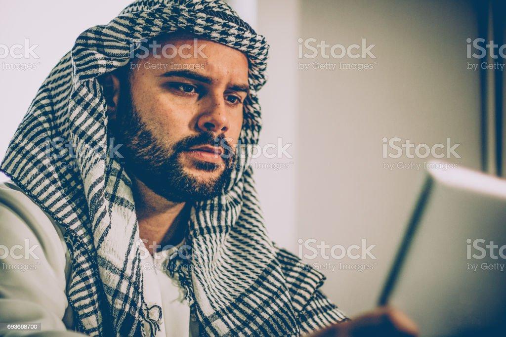 Jeune homme arabe en regardant ordinateur portable au bureau