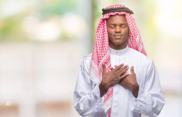 junge arabische afrikaner tragen traditionelle kufiya über isolierte hintergrund lächelnd mit die hände auf die brust mit geschlossenen augen und dankbar geste auf gesicht. gesundheitskonzept. - die wahrheit tut weh stock-fotos und bilder