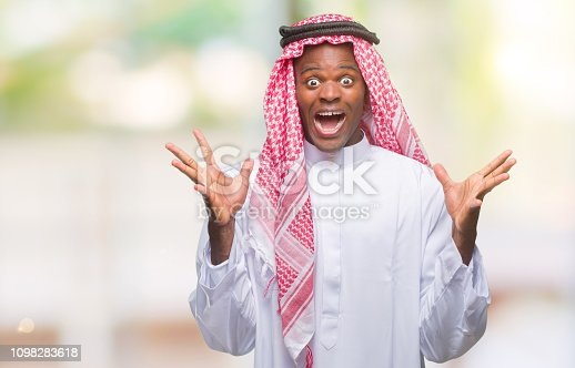 istock Young arabic african man wearing traditional keffiyeh over isolated background celebrating crazy and amazed for success with arms raised and open eyes screaming excited. Winner concept 1098283618
