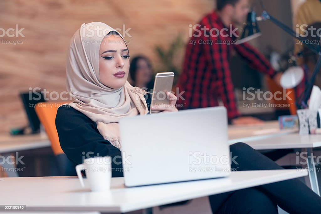 Young Arabic business woman wearing hijab,working in startup office. stock photo