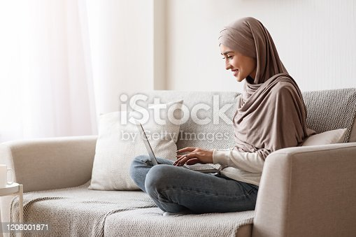 Remote Work Concept. Young Arabic Woman Freelancer In Hijab Using Laptop At Home, Typing On Keyboard, Sitting On Cozy Sofa, Side View