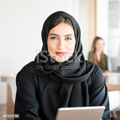 Arab businesswoman at work. Young Arab female in business office holding digital tablet. She is wearing traditinal Emirati Middle Eastern