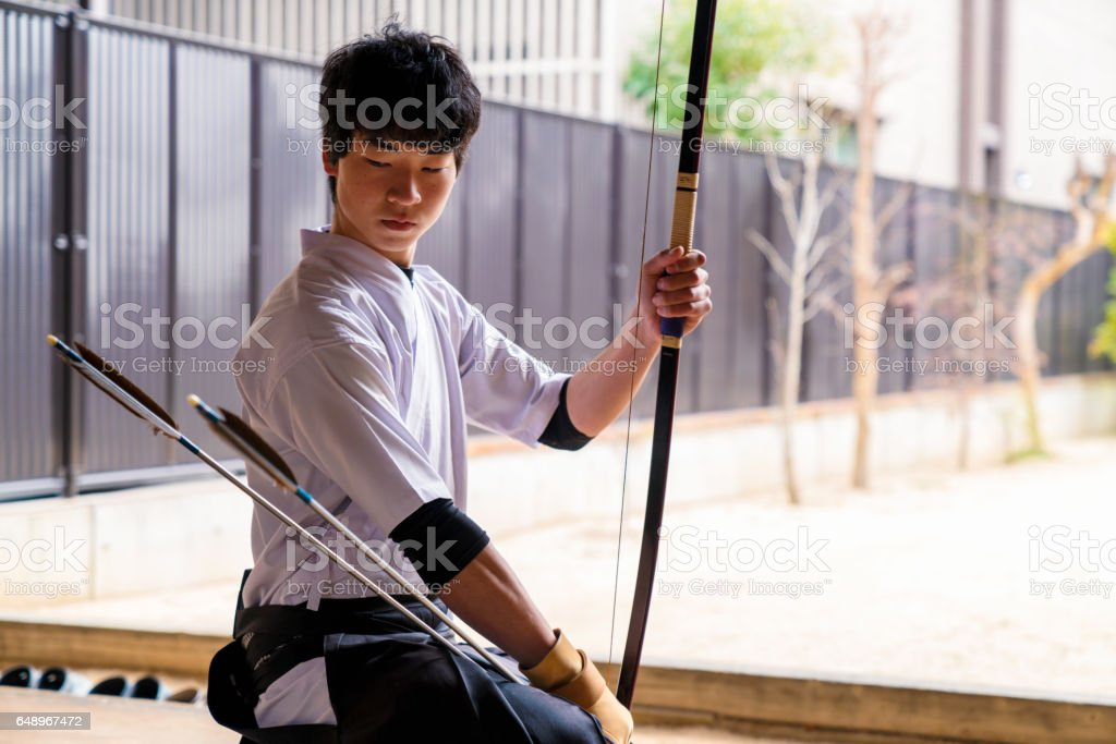Young archer inspecting his arrows stock photo