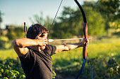 Young archer training with the bow in a city park
