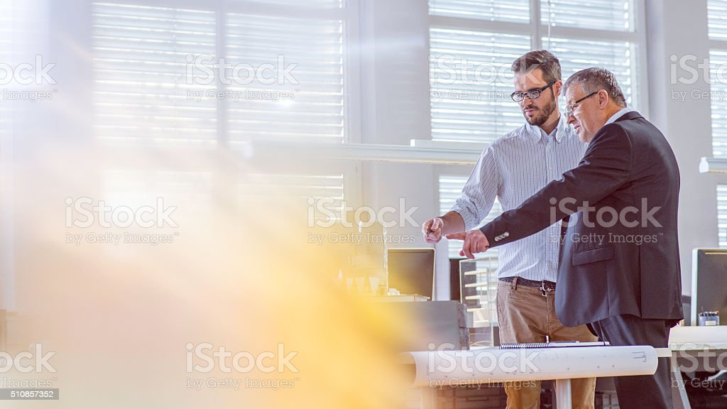 Young architect discussing project with his client stock photo