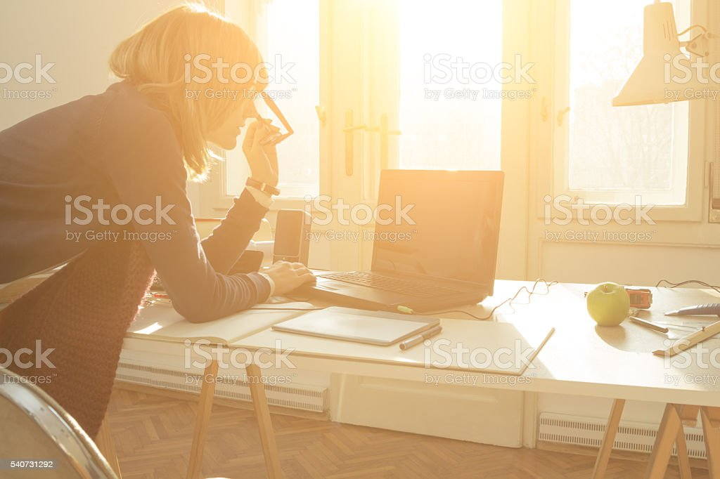 Young architect doing work in her sunny studio. stock photo