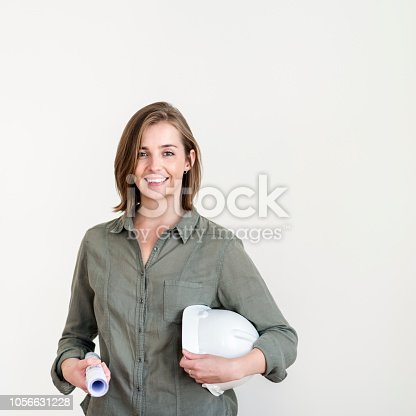 Confident young architect standing while holding blueprint and hardhat. Portrait of beautiful female building contractor. She is against black background.