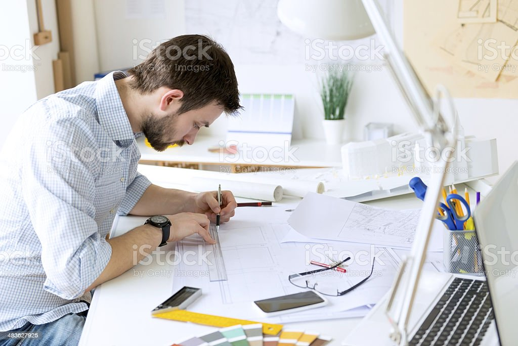 Young male architect working on a new project. Horizontal shot.