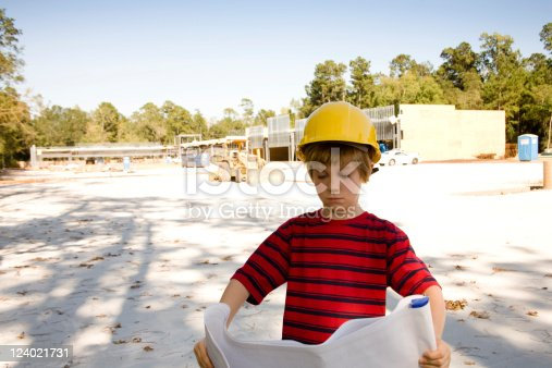 istock Young architect reading blueprints wearing hardhat at jobsite 124021731