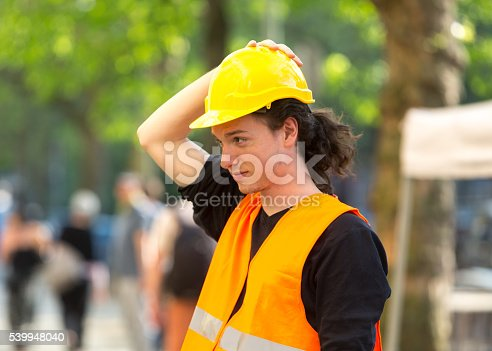 istock Young architect wearing safety jacket putting on his yellow hardhat 539948040