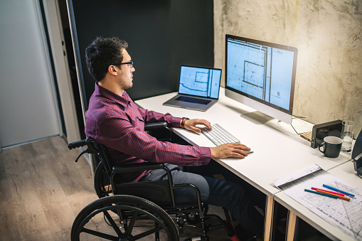 Man with differing abilities working in the office while sitting in his wheelchair