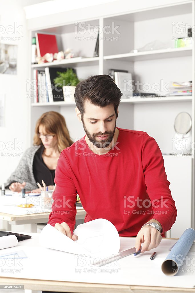 Young businessman working in small architect studio.